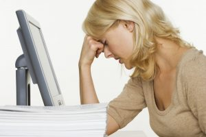 Frustrated woman at desk with pile of papers beside her